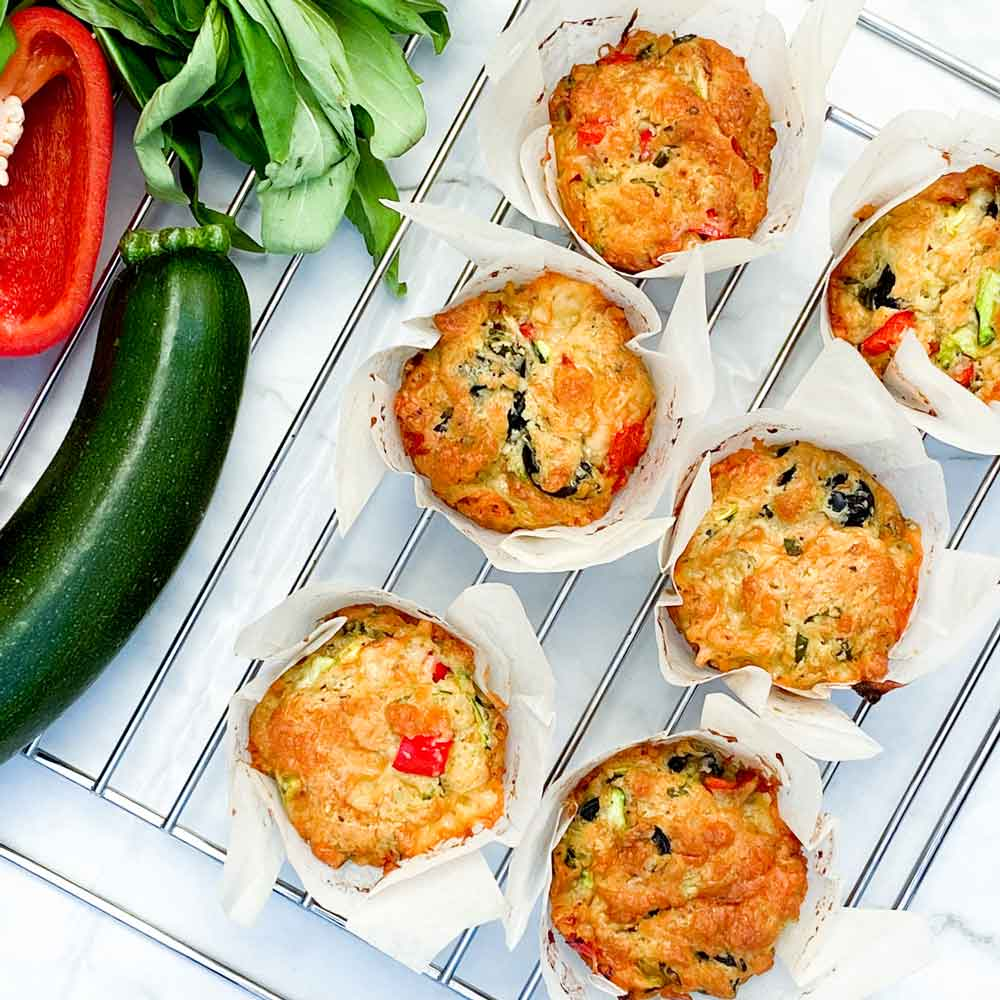 6 cheddar muffins on a tray with vegetables