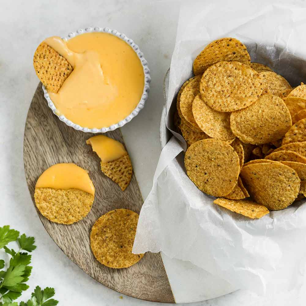 Nacho cheese sauce and nacho crackers presented for serving.